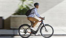 Mann mit Rucksack in der Stadt auf einem E-Bike Trek Allant+